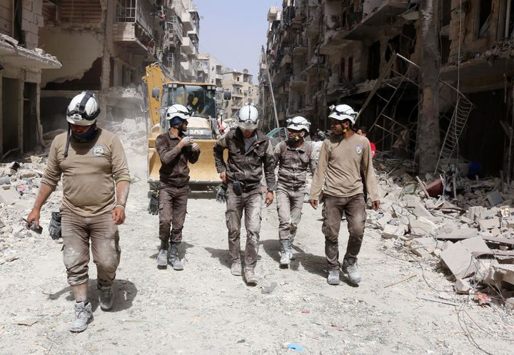 Members of the White Helmets walk amid the debris following a reported airstrike by Syrian government forces in Aleppo on Jun