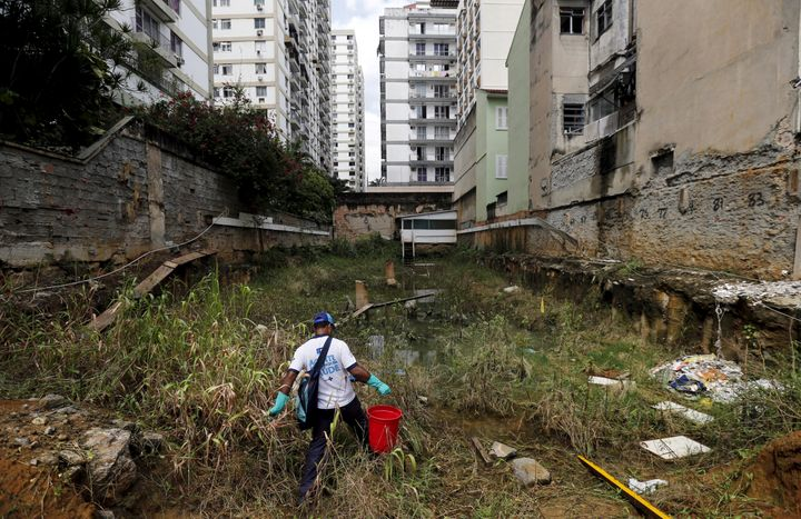 A health agent carries a bucket of guppy fish to place them in standing water to consume larva of Zika-transmitting mosquitoes in an empty lot of Rio de Janeiro's Tijuca neighborhood, Brazil, February 17, 2016.