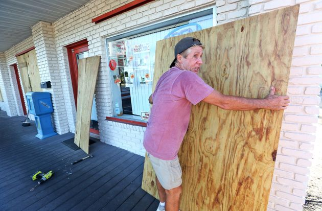 A man boards up a house in Cape Canaveral ahead of Matthew's anticipated arrival on Thursday