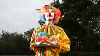 Clown holding plastic balls, standing on lawn