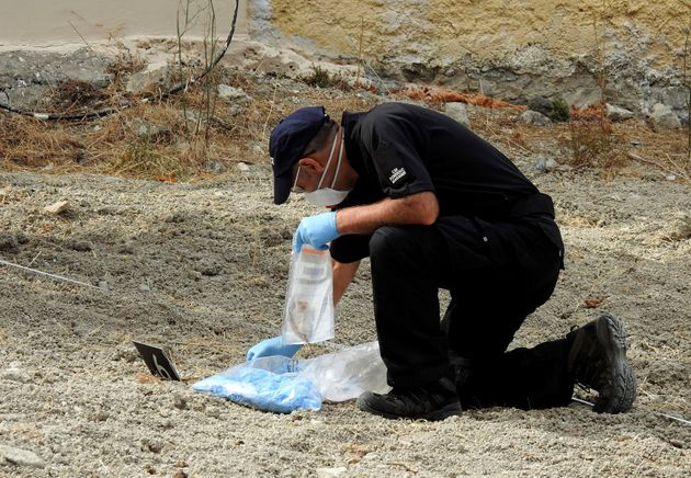 A police officer collects potential clues during the search for Ben