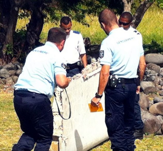 Officials carry the flaperon which washed up on Reunion Island