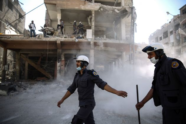 Syrian civil defence volunteers, known as the White Helmets, work around destroyed buildings following...