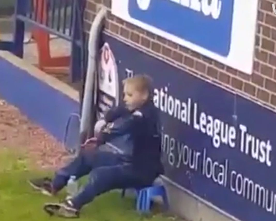 The ball boy performs a dance routine while sitting on a plastic stool during a Stockport County