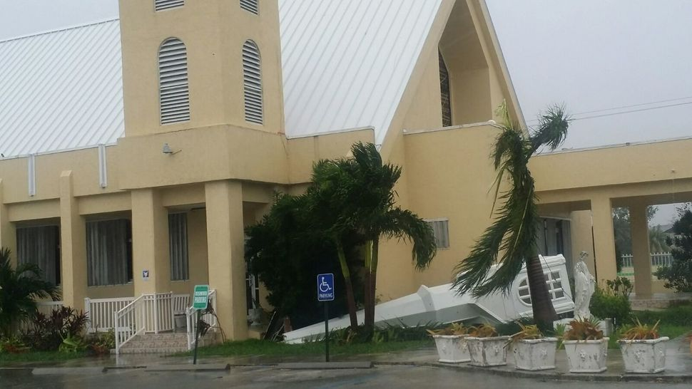 A toppled steeple is seen at St. Gregory's Parish in Nassau, New Providence island, in the Bahamas, on Thursday.