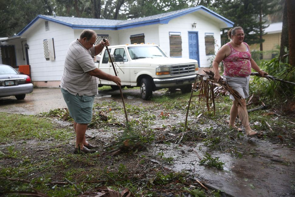 Jim Griggis (L) and Marlin Whaley clean up after Hurricane Matthew passed through the area in Fort Pierce, Florida.