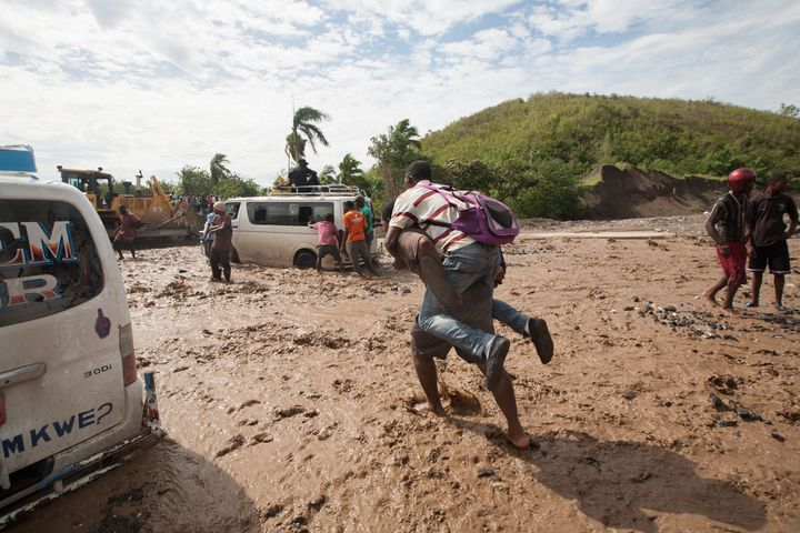 People trying to walk or drive through a river in Haiti after a nearby bridge collapsed because of the hurricane.