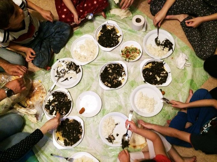 Inside their shelter room, sisters Toulin and Yasmin gather with their family for a dinner of rice and molokhia, a vegetable