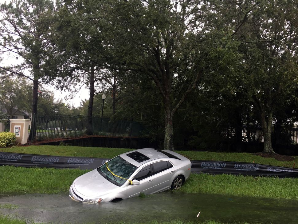 A car rests in a ditch off 17/92 in the Longwood/Lake Mary area in front of the Wyndham Place apartments on Friday in Longwoo