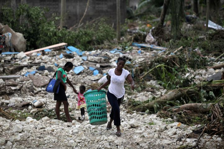 A woman carries a laundry basket in an area devastated by Hurricane Matthew in Cavaillon, Haiti, Oct. 6, 2016.