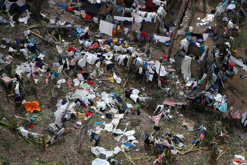 People try to dry clothes in the sun at their destroyed houses after Hurricane Matthew passes Jeremie, Haiti, October 6, 2016