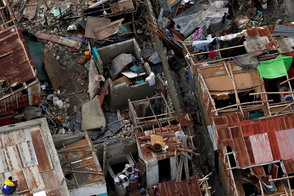 People try to rebuild their destroyed houses after Hurricane Matthew passes Jeremie, Haiti, October 6, 2016.