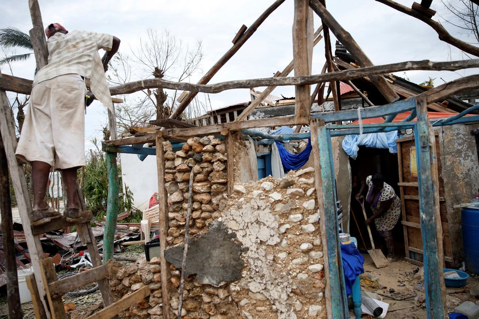 People try to rebuild their destroyed house after Hurricane Matthew passed Jeremie, Haiti, October 6, 2016.