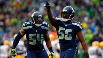 SEATTLE, WA - JANUARY 18:  Cliff Avril #56 and  Bobby Wagner #54 of the Seattle Seahawks celebrate against the Green Bay Packers  during the 2015 NFC Championship game at CenturyLink Field on January 18, 2015 in Seattle, Washington.  (Photo by Tom Pennington/Getty Images)