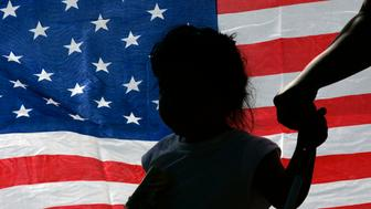 A child is silhouetted against a U.S. flag at a rally in support of immigration rights in Irving, Texas October 13, 2007.  Opposing sides came out to express their views about a controversial program used by the Irving Police Department which hands undocumented workers over to federal officials for deportation proceedings. REUTERS/Jessica Rinaldi (UNITED STATES)