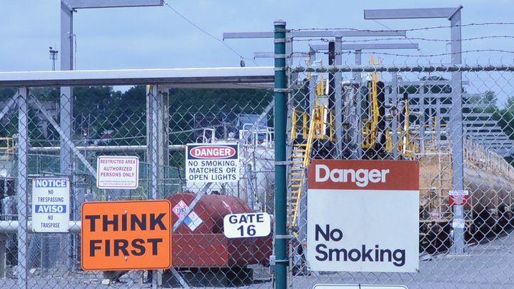 A medley of caution signs is posted on a barbed-wire fence near the Global Partners Albany Terminal, where crude oil from tra