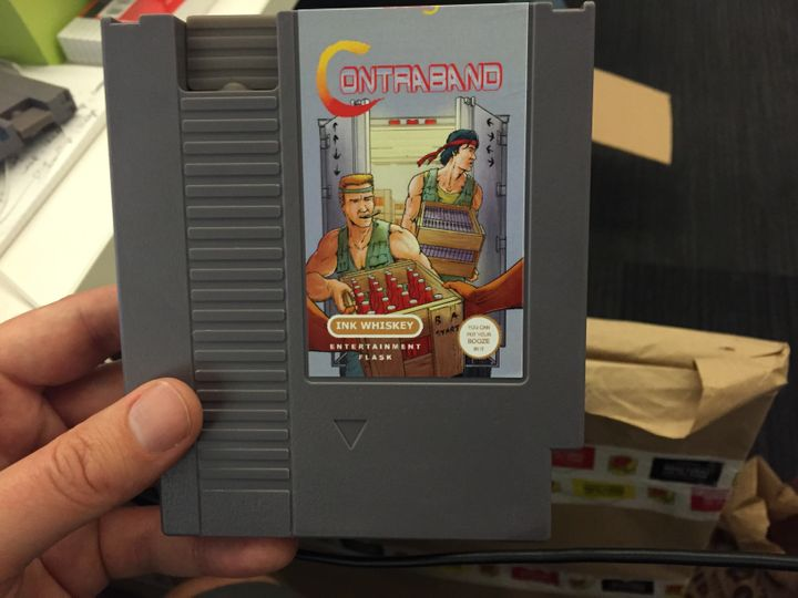 """ANintendo cartridge flask parodying the classic game """"Contra."""""""