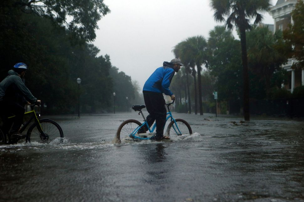 Residents on bikes make their way through a flooded street on Oct. 8, 2016 in Charleston, South Carolina.