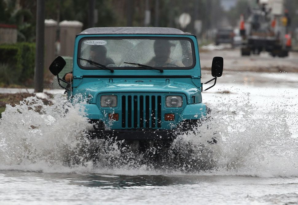 A Jeep drives down a flooded street on Oct. 8, 2016 in Jacksonville Beach, Florida.