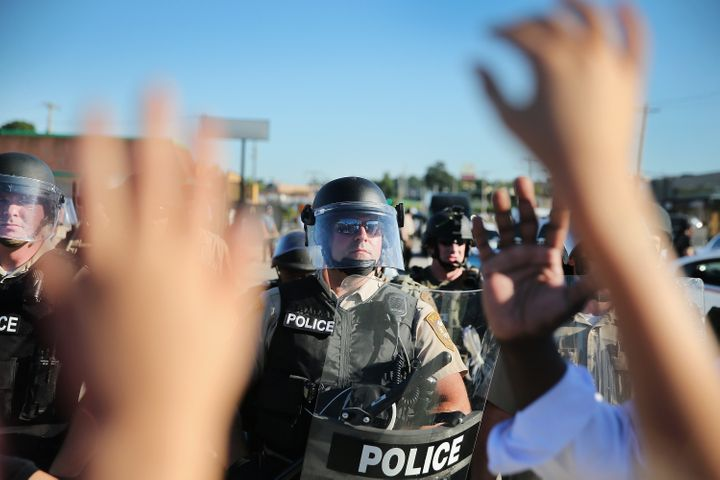 A child holds up her hands after police ordered protesters off the street on Aug. 13, 2014, in Ferguson, Missouri.