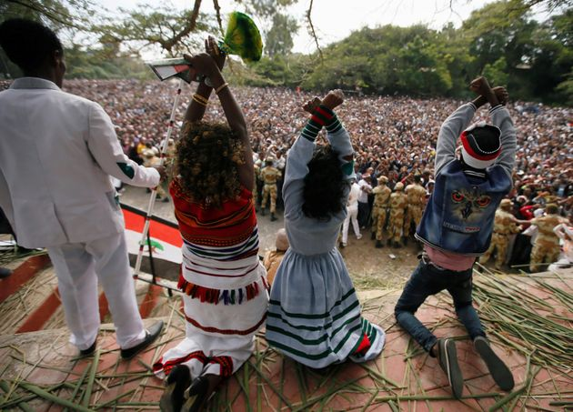 Demonstrators chant slogans while flashing the Oromo protest gesture during Irreecha, the thanksgiving...