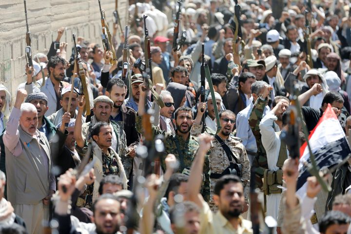 Armed people demonstrate outside the United Nations offices against Saudi-led air strikes on funeral hall in Sanaa, the capit