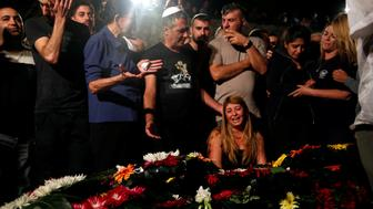 Relatives and friends mourn over the grave of Israeli policeman Yosef Kirma who was killed by a Palestinian assailant who fired from a car before being shot dead by Israeli police in Jerusalem, at Mount Herzl cemetery in Jerusalem October 9, 2016. REUTERS/Ronen Zvulun