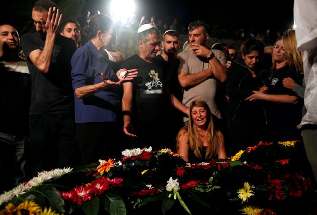 Relatives and friends mourn over the grave of Israeli policeman in Jerusalem October 9,