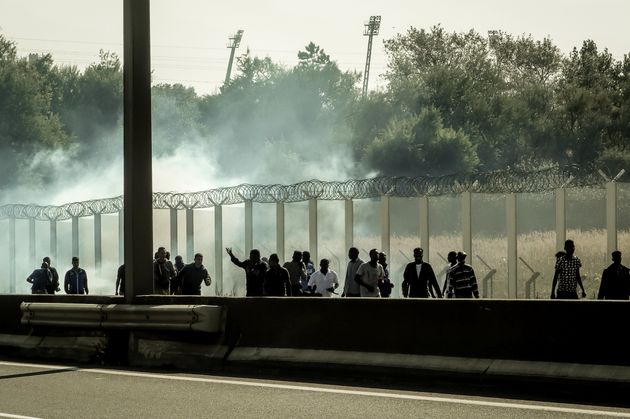 Migrants run away from tear gas during clashes with riot police trying to prevent them from getting into...