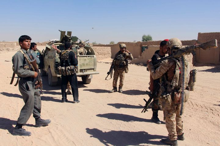 Afghan Special Forces and policemen prepare themselves for battle with the Taliban on the outskirts of Lashkar Gah capital of