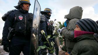 "Youngs migrants holding white flowers face French riot police officers who secure the area near makeshift shelters during the partial dismantlement of the camp for migrants called the ""Jungle"" in Calais, France, March 7, 2016.    REUTERS/Pascal Rossignol"