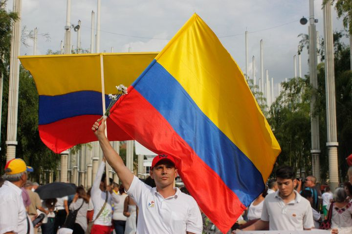 Pro-peace supporter waves the Colombian flag as he joins thousands of others in the Park of Lights in downtown Medellín on Oc