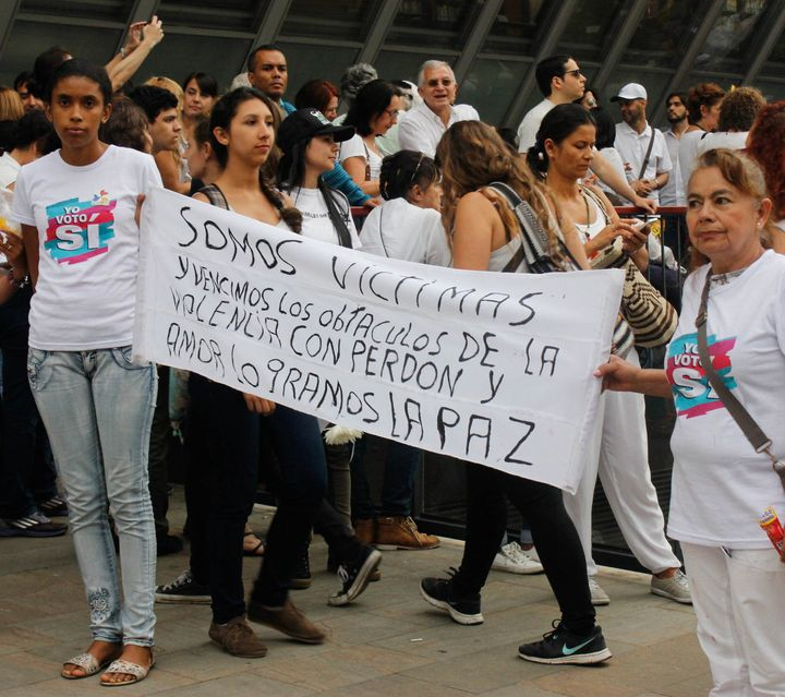 """Yenny Hernandez and Blomia Perez Alvaréz of the Network for Women Victims and Professionals hold a banner that reads, """"We are victims and we overcame obstacles of violence with forgiveness and love. We will achieve peace"""" while joining pro-peace festivities ahead of an October 7 march in Medellín."""