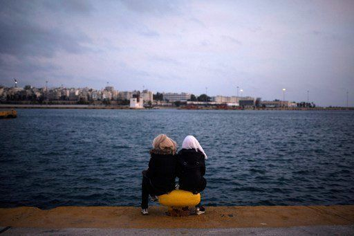 Two women from Syria sit facing the sea in Athens in March 2016.