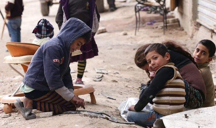 Syrian refugees play in the streets of Damascus on February 18, 2015.