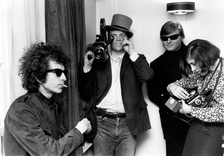 Pennebaker, holding a camera and wearing a top hat, with Bob Dylan.