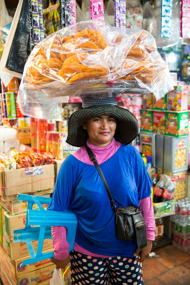 A woman sells bread from a basket she balances on her head