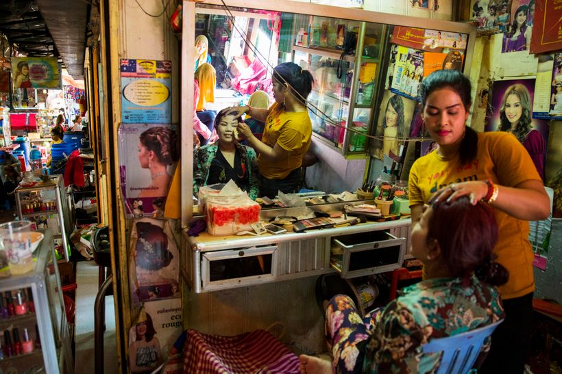 A woman gets primped at a beauty salon in the market