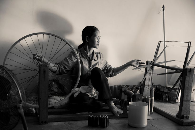 A woman weaving silk in fashion designer, Eric Raisina's design studio