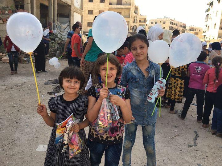 Syrian schoolchildren in Aleppo pose with their white balloons.