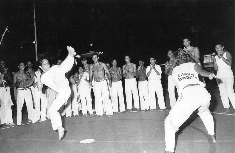 Professora Pimentinha (left) playing in a Capoeira roda with Ginga Mundo Mestre Sabia (center) looking in Bahia, Brazil.