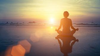 Yoga, fitness and healthy lifestyle. Silhouette meditation girl on the background of the stunning sea and sunset. Woman doing meditation near the ocean. Yoga silhouette.
