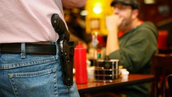Bryan Hull, founding director of the Oklahoma Open Carry Association (OKOCA), wears an unconcealed side arm as he addresses OKOCA members gathered at Beverly's Pancake House in Oklahoma City November 1, 2012. A new Oklahoma law took effect November 1 allowing anyone with a concealed weapon license to carry their firearms openly in a holster or belt.   REUTERS/Bill Waugh   (UNITED STATES - Tags: SOCIETY POLITICS CRIME LAW)