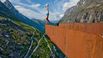 TROLLSTIGEN, NORWAY - JULY 03. EXCLUSIVE: Eskil performing a handstand at the look out over Trollstigen on July 03, 2010 in Norway. Stomach-churning images show how danger man Eskil Ronningsbakken, 30, shows no fear as he balances on the edge of a plunging cliff face at 1,400 metres - incredibly on a unicycle. In the extreme artist's latest stunts seen earlier this month he also teeters on a pile of chairs set on a boulder wedged precariously between two rock faces at 1,000 metres altitude, and balances 300 metres above a lake with one of his students, Kenyan Moses Wepukhuli, 25. All of the amazing feats were caught on camera at lofty locations around Norway. Sure-footed Eskil, a Norwegian, has been pulling off his jaw-dropping balancing acts around the world for 15 years. Sometimes walking for up to six hours to get to the locations for his acts, Eskil uses yoga to train and prepare for his bold shapes in dangerous places. (Photo by Sindre Lundvold / Barcroft Media / Getty Images)