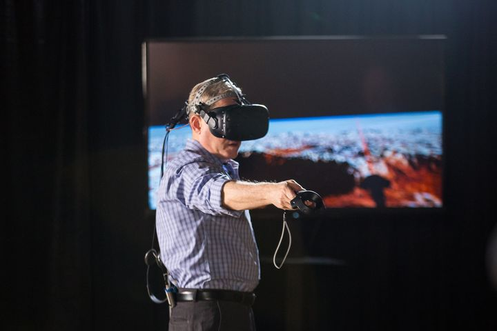 Alan Stern, a NASA scientist who led the mission for the exploration of Pluto, checks out the Pluto VR experience.