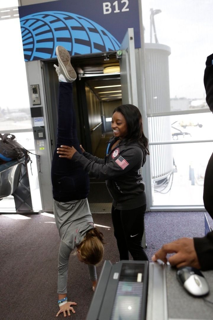 Simone Biles helps a passenger into a handstand at O'Hare International Airport.