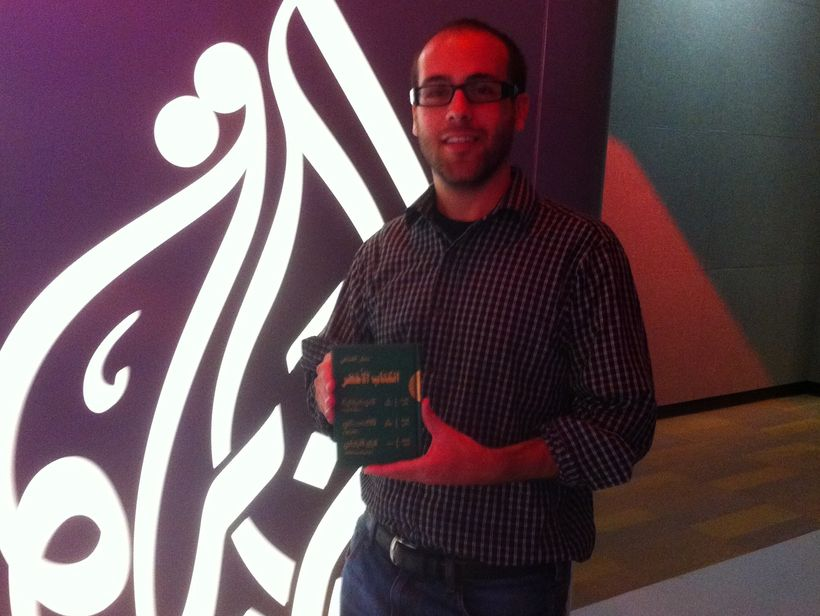 """In the Al Jazeera English newsroom, holding a copy of Muammar Gaddafi's infamous """"Green Book"""" brought back from Libya by corr"""