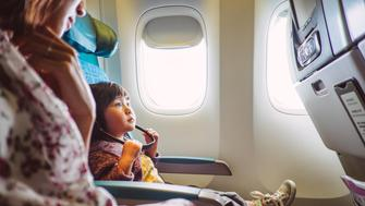 Lovely little girl wearing the headphone looking at the seat-back TV screen concentratedly with mom on the airplane