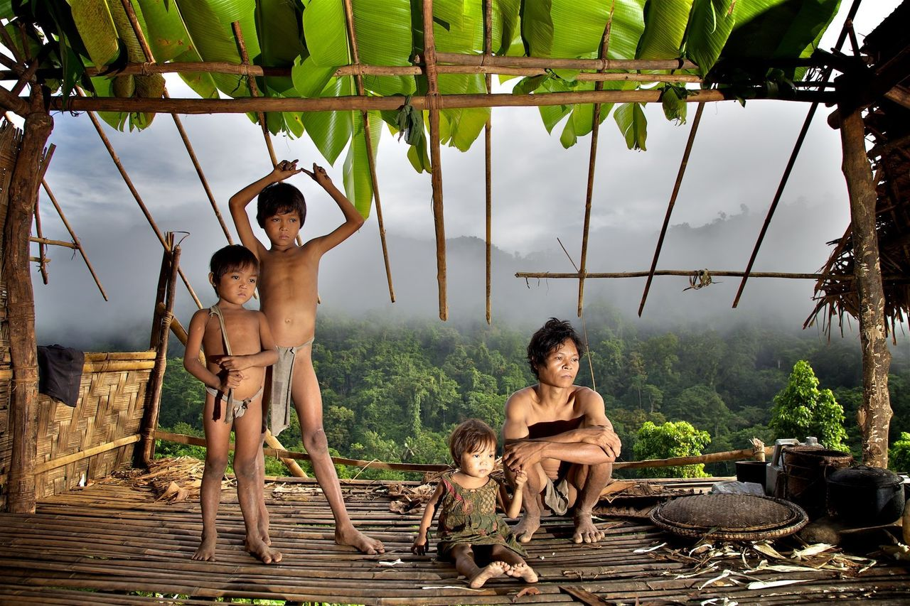 A father and daughter look down over the Singapan Valley from their house. Taut Batu tribe, Palawan, Philippines.