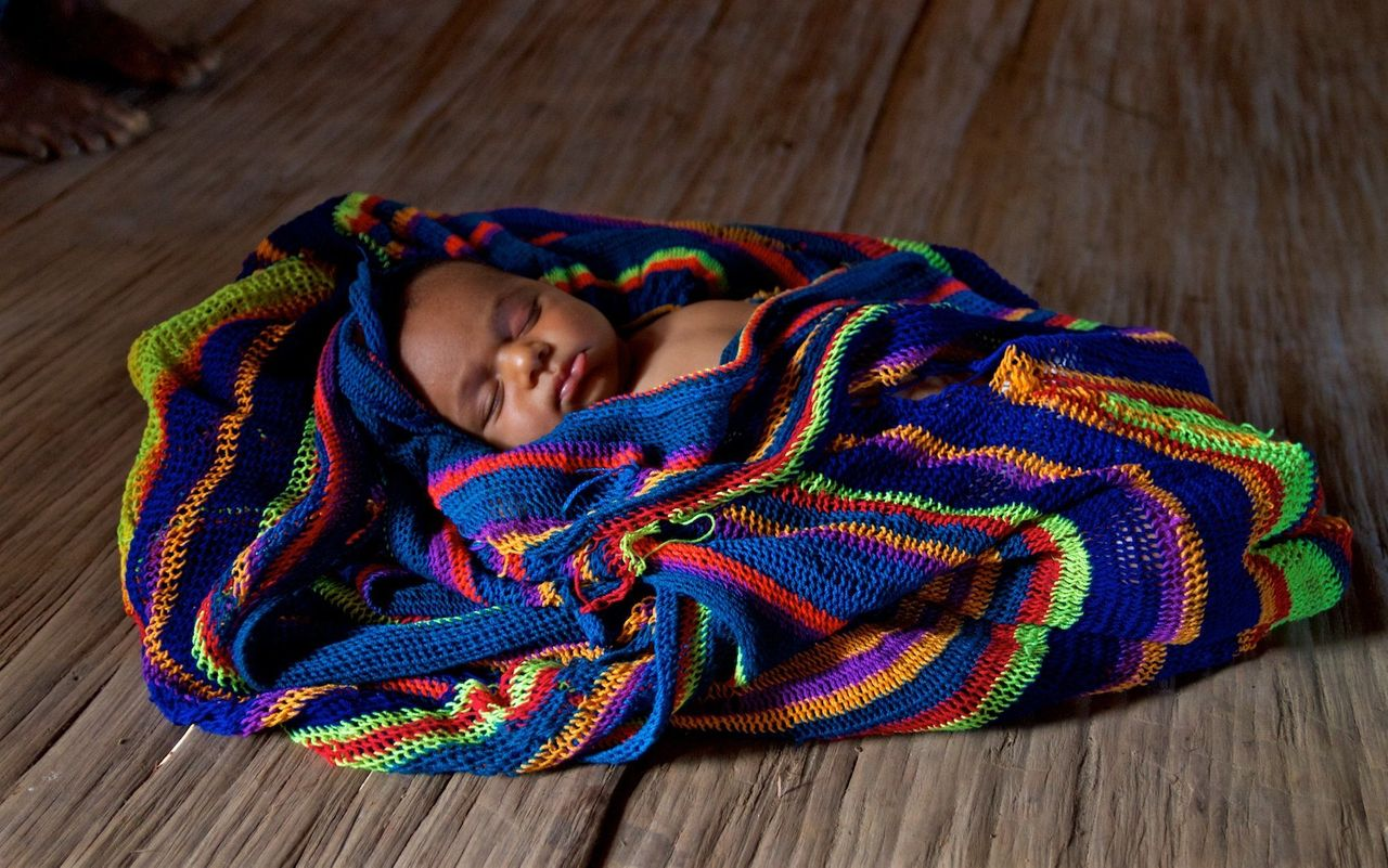 Sibilato's newborn daughter sleeps in a traditional woven bilum. Bosavi region, Southern highlands, Papua New Guinea.